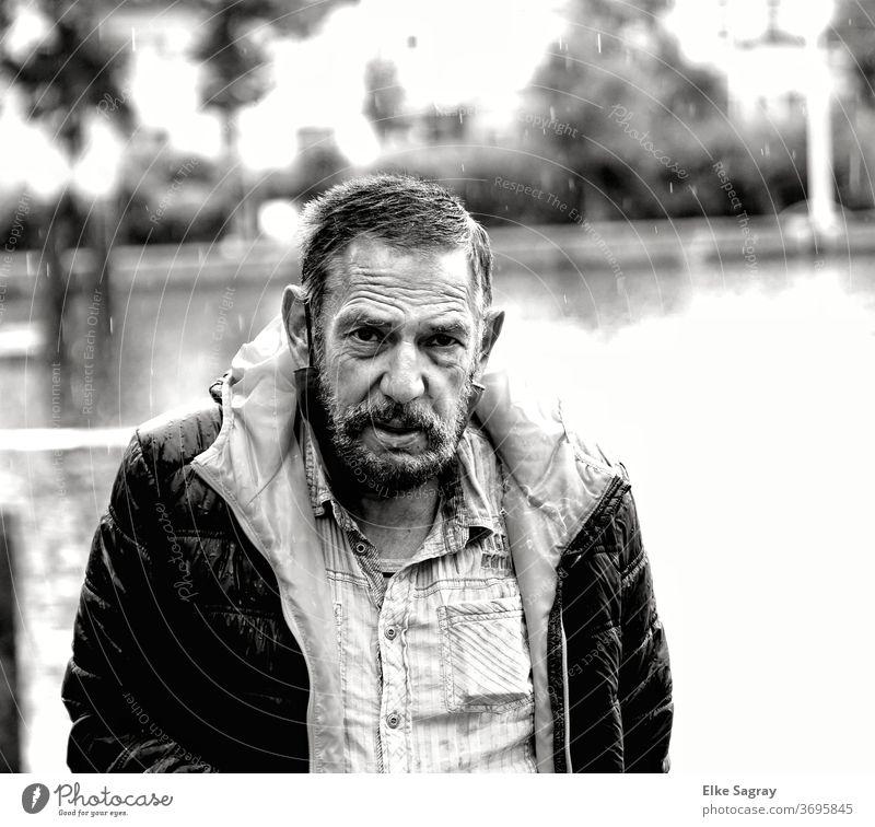 Menschen unter uns- Mann im Regen Ein Mann allein 1 Mensch Schwarzweißfoto Wasseroberfläche Außenaufnahme