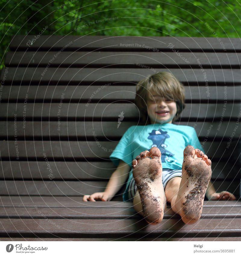 dreckige Füße - Junge sitzt mit schmutzigen Füßen auf einer Bank | Lieblingsmensch Kind Fußsohlen Waldboden barfuß Freude Spaß Holz Lachen Nahaufnahme