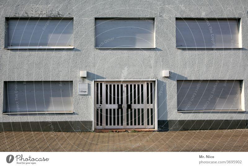5 Fenster und eine Tür Fassade Haus Gebäude Architektur Rolladen Schatten Mehrfamilienhaus keiner da keiner zu hause Bürogebäude weiß geschlossen