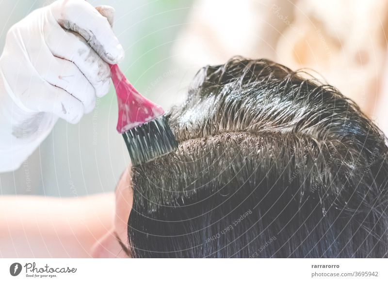 eine junge brünette, kaukasische Frau, die sich zu Hause mit einer rosa Bürste und weißen Handschuhen die Haare färbt Behaarung Schönheit Farbstoff Farbe