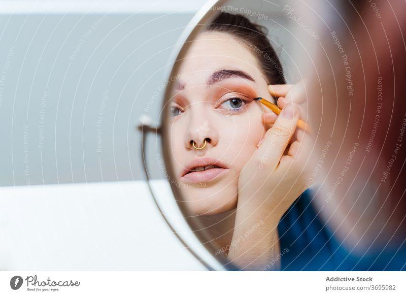 Frau macht Make-up zu Hause bewerben Kajal Gesicht Kosmetik dekorativ Tisch Bürste Tablette heimwärts Stil professionell Konzentration Zeitgenosse Schönheit