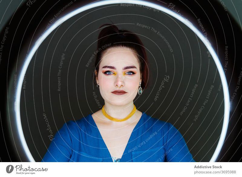 Frau mit Ringleuchte im Studio kreisen Lampe Model Atelier leuchten Licht glühen Halt Stil trendy Make-up professionell emotionslos jung elegant Lächeln