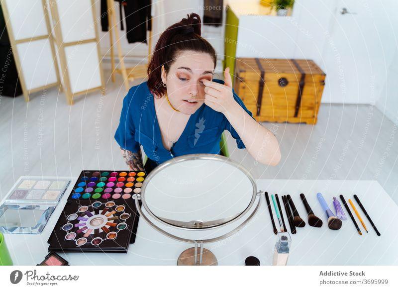 Frau macht Make-up zu Hause bewerben Lidschatten Gesicht Spiegel Kosmetik Künstler visagiste professionell Tisch sortiert Glamour sitzen Produkt Stil Pflege