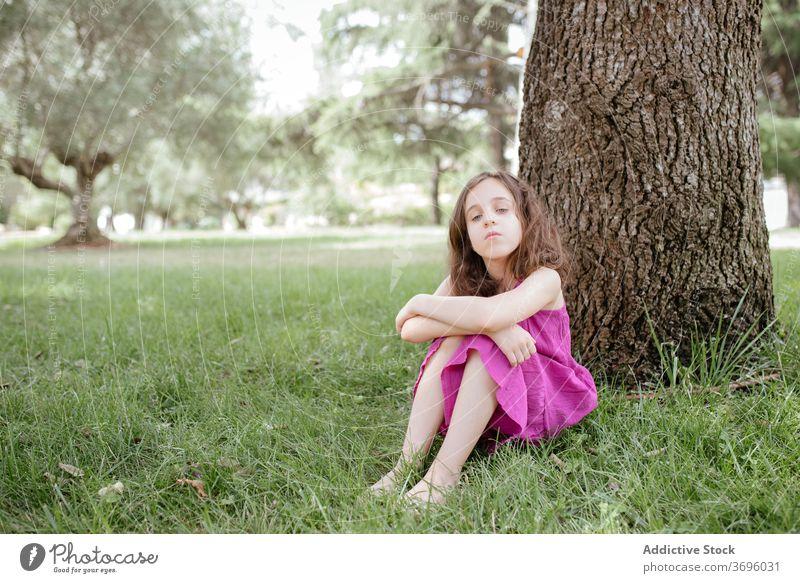 Kleines Mädchen sitzt unter Baum im Park ruhen Natur sitzen sich[Akk] entspannen ruhig Windstille Kind Sommer Gras Lifestyle Harmonie Rasen Gelassenheit