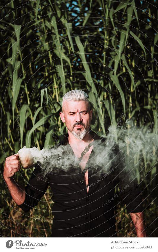 Älterer bärtiger Mann mit Rauchbombe im Feld stehend brutal ernst Vollbart selbstbewusst Bestimmen Sie stark Porträt Erwachsener männlich Tattoo graues Haar
