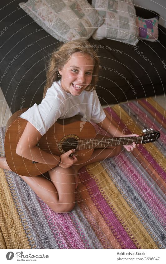 Mädchen sitzt auf dem Boden spielen eine Gitarre, während ist lächelnd und mit Blick auf die Kamera vertikal Musik Künstler Klassik Lernen Musiker Spielen üben