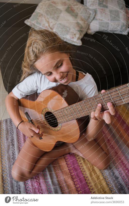 Mädchen sitzt auf dem Boden eines Hauses spielen eine Gitarre mit glücklichen Ausdruck Musik Künstler Klassik Lernen Musiker Spielen üben Raum Lächeln Schnur