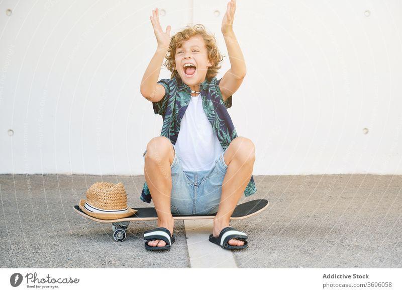 Kind in Sommerkleidung sitzt auf einem Skateboard und gestikuliert freudig dynamisch extrem Fähigkeit Vitalität Skater Skateboarderin Jugendzeit Gleichgewicht