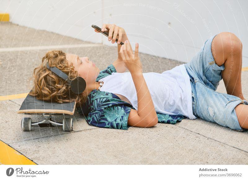 Junge auf dem Boden liegend mit einem Skateboard, der Musik hört und auf sein Handy schaut Jugendzeit zuhören Einsamkeit Gesang Stilrichtung Generation Teenager
