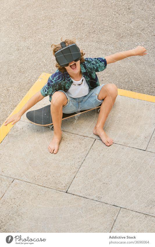 Junge sitzt auf einem Skateboard, trägt eine Virtual-Reality-Brille und gestikuliert, während er fliegt vertikal Reaktionen u. Effekte berührend gestikulierend