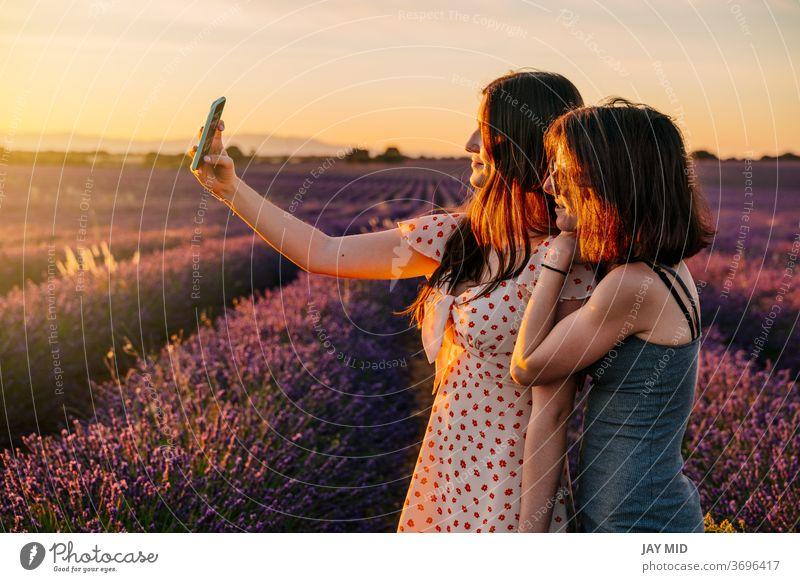 Zwei Freunde fotografieren mit ihrem Handy in einem Feld mit blühenden Lavendeln Frau... zwei Feiertag Fotos machen Telefon Selfie Sommer Urlaub Blüte genießen