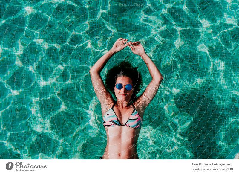 Draufsicht auf eine glückliche junge Frau, die in einem Pool schwebt. Sommer und lustiger Lebensstil unter Wasser Schwimmsport Blasen Spaß Kaukasier Sinkflug