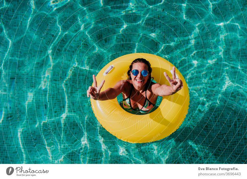 Draufsicht auf eine glückliche junge Frau, die in einem Pool in einem gelben Donut schwimmt. Sommer und lustiger Lebensstil gelbe Donuts aufblasbar Schwimmsport