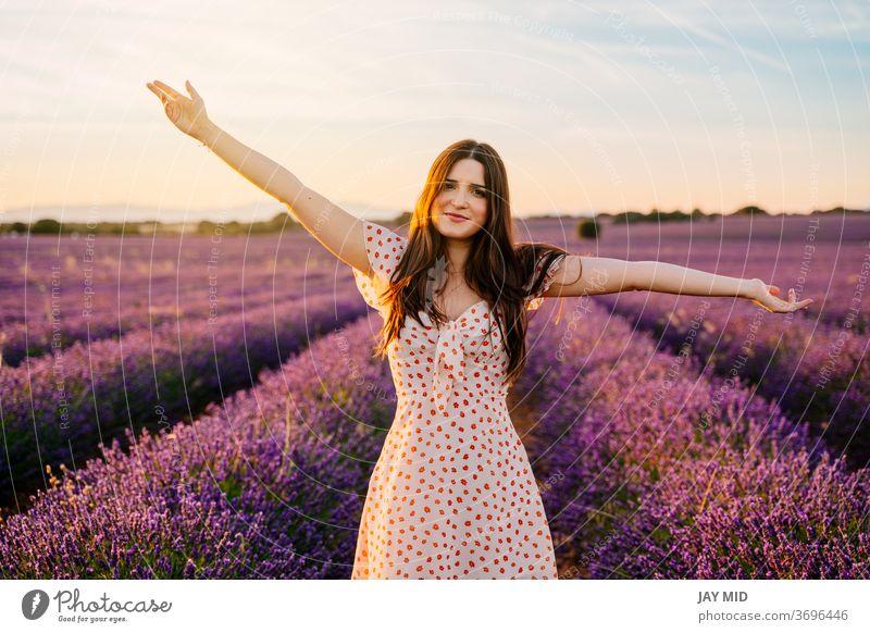 Glückliche Frau in einem Kleid und mit offenen Armen im Lavendelfeld. offene Arme schön Fröhlichkeit Feld Freiheit Lächeln jung Natur purpur Frühling Model