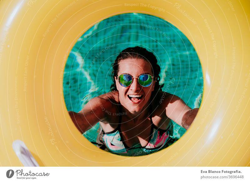 Draufsicht einer glücklichen jungen Frau in einem Pool mit einem gelben Donut in der Hand. Sommer und lustiger Lebensstil gelbe Donuts aufblasbar Schwimmsport