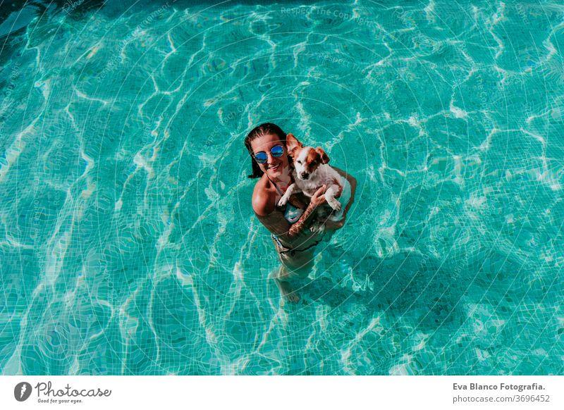 glückliche junge Frau und Hund in einem Schwimmbad, die Spaß haben. Sommerzeit Blauwasser Liebe jack russell Hut Zusammensein Zusammengehörigkeitsgefühl Kuss