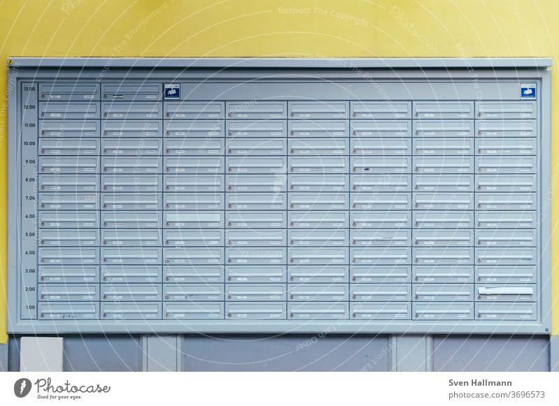 viele Briefkästen vor gelber Wand Briefkasten Post Metall Farbfoto Menschenleer Schlitz Kommunizieren Außenaufnahme Klappe Hochhaus anonym