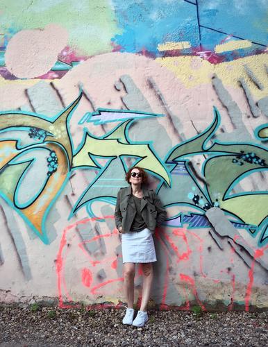 Frau mit Sonnenbrille vor einer Wand mit Graffiti Sneaker gelockt rothaarig Außenaufnahme Tag Mensch Mode grün khakigrün bunt Muster anlehnen cool Junge Frau
