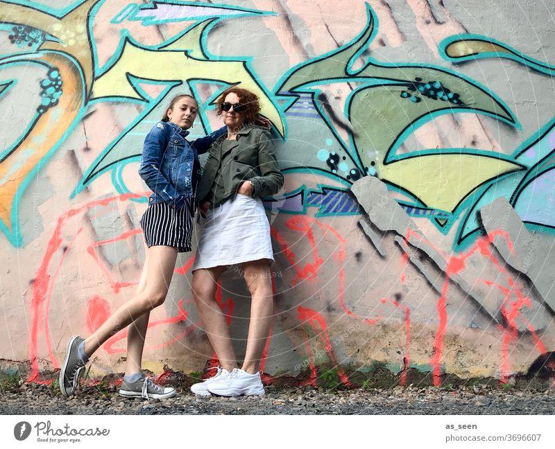 Zwei Frauen vor einer Wand mit Graffiti Sneaker Sonnenbrille gelockt rothaarig Außenaufnahme Tag Mensch Mode grün khakigrün bunt Muster anlehnen cool Coolness