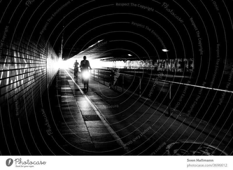 Radfahrer im Tunnel Verkehr Großstadt Geschwindigkeit Außenaufnahme fahren Ausflug Schattenspiel Straße urban Lifestyle Transport Fahrradfahren Bewegung Kunst