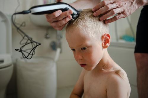 Vater schneidet dem Sohn zu Hause die Haare Behaarung Haarschnitt heimwärts Frisur Kind Pflege Maschine Bad Familie Hand geschnitten Friseur Mann Trimmer