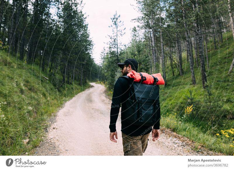 Junger männlicher Naturforscher geht auf dem Feldweg durch den Wald aktiv Abenteuer Rucksack Backpacker Rucksacktourismus Landschaft Schmutz erkunden Entdecker