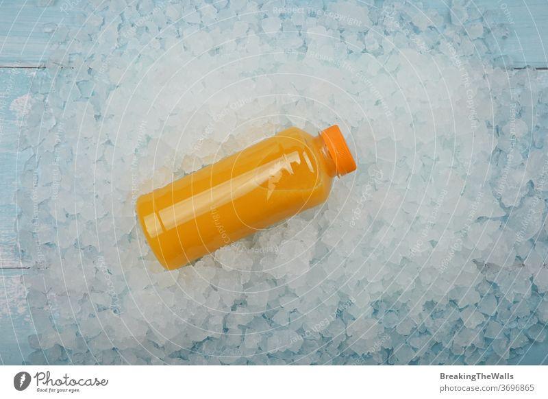 Flasche mit frischem Orangensaft über zerstoßenem Eis orange Saft eine Kunststoff Haustier satt gequetscht gepresst zerdrückt Hintergrund Nahaufnahme blau weiß