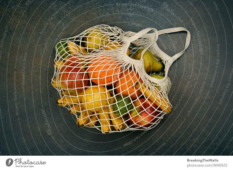 Verschiedene frische Früchte in einer Einkaufstasche mischen sortiert orange Apfel Banane Zitrone Kalk Birne kaufen Tasche Netz ineinander greifen Schnur Öko
