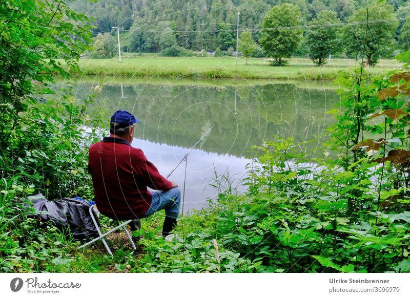Angler sitzt am Flussufer im Grünen Angeln Wasser Fischer Ansitzen Ufer Gebüsch Wald grün Erholung Stille Ruhe Fische fangen Freizeit & Hobby Natur warten