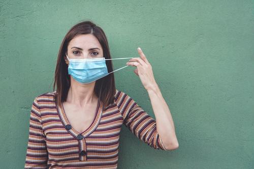 Frau mit medizinischer Maske, die eine medizinische Schutzmaske hält Coronavirus Junge Frau Virus Seuche Pandemie Quarantäne covid-19 Symptom Medizin Gesundheit