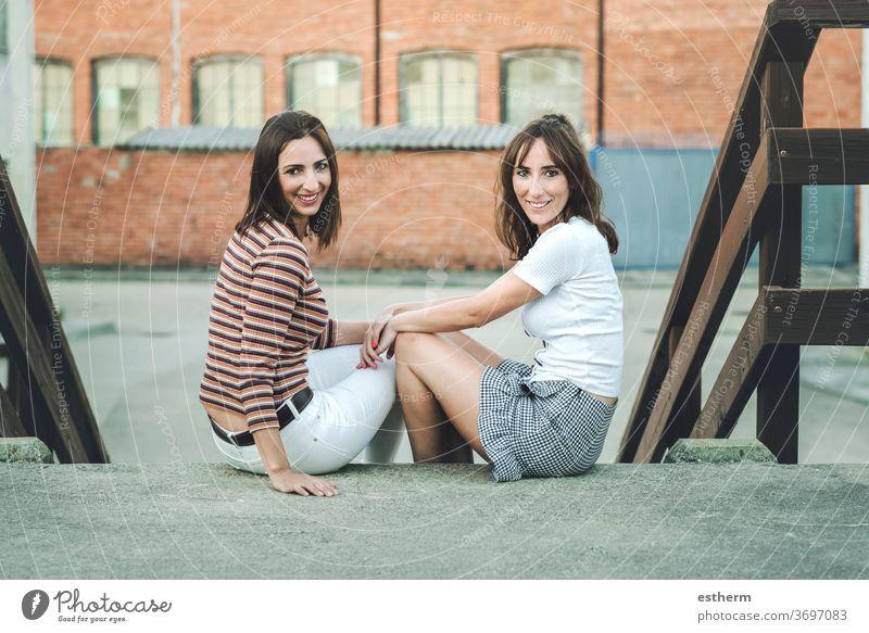 junge Freundinnen, die auf der Straße sitzen Junge Frauen Freunde Zwei Personen Stehen Schwester urban lustig Feiertag reisen im Freien Schönheit Mode Leben