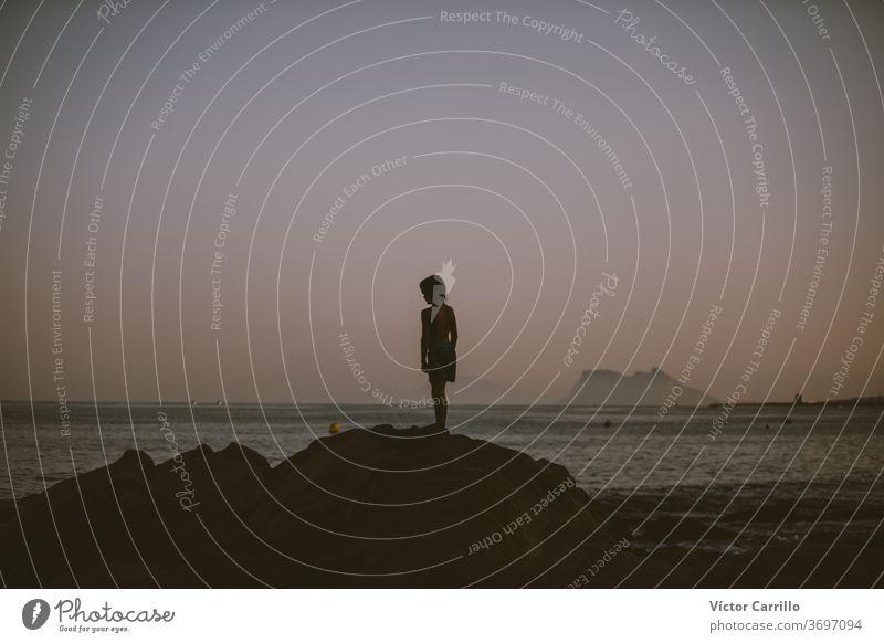 Ein Junge, der in der untergehenden Sommersonne auf das Meer schaut Strand-Landschaft Vertrauen Farbe kommt Unschärfe glauben Denken Leben Moment geduldig Mann
