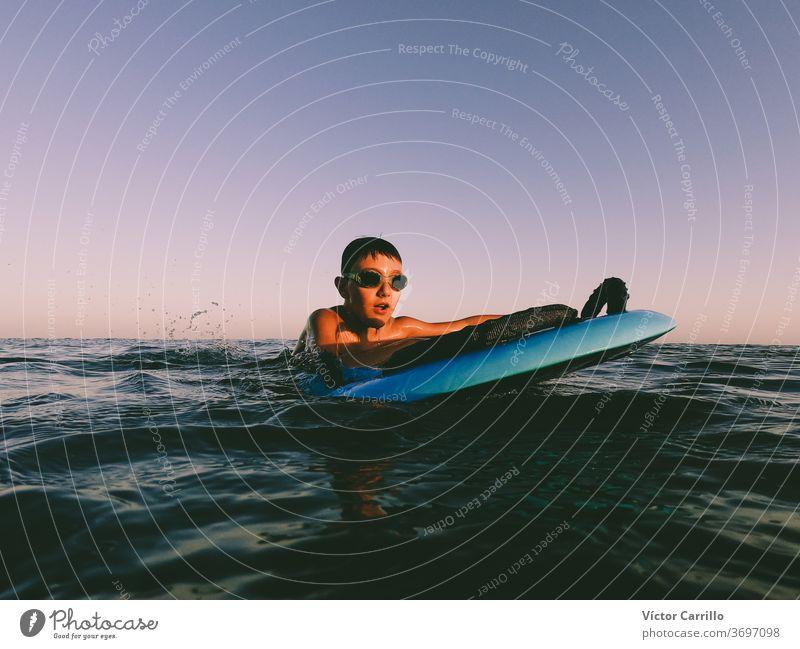 Ein kleiner Junge lernt an einem sonnigen Sommertag draußen an der Küste im Bodyboard bodyboarder Kind Feiertag Urlaub Freizeit Ufer Lifestyle Surfbrett
