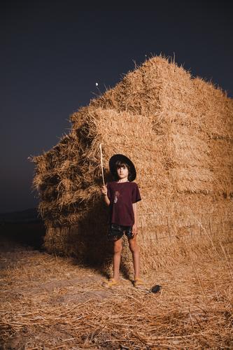 Ein Junge mit Hut, der im Sommer auf den Feldern auf dem Land in einem Strohballenhintergrund spielt Bauernbursche hockend Pflanze Spielen Herbst Kind niedlich