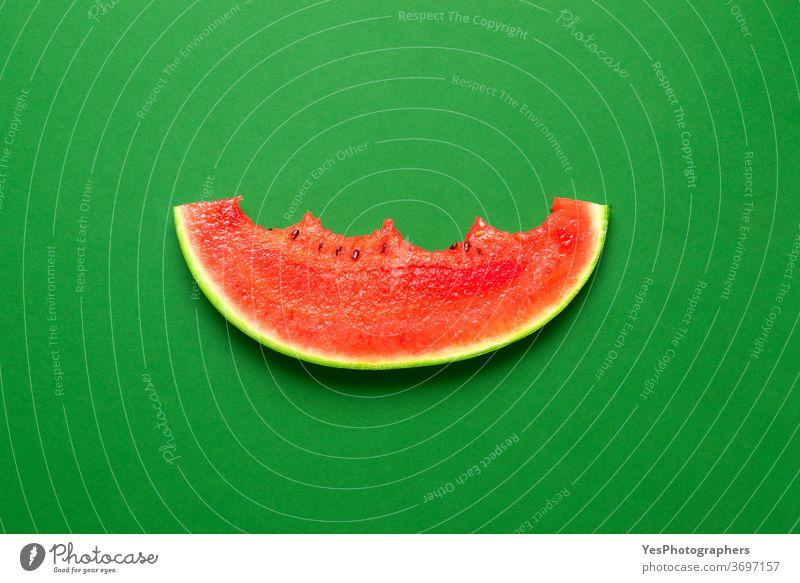 Isolierte Wassermelonenscheibe auf grünem Hintergrund. Gebissene Wassermelonenscheibe in der Draufsicht. obere Ansicht gebissen farbig farbenfroh geschnitten