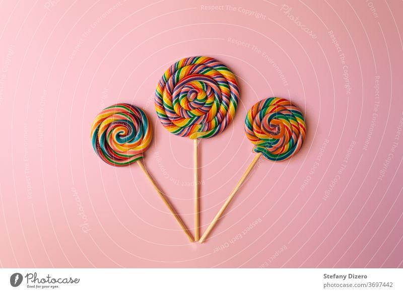 Bunte Strudel-Lollipops auf rosa Hintergrund angeordnet. Geburtstag Bonbon Kindheit Farbe farbenfroh niedlich lecker Dessert flach flache Bauweise Lebensmittel