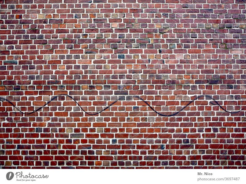 Wellenlinie auf einer Backsteinmauer Wand Mauer Backsteinwand Haus Mauerwerk Ziegelwand Altbau Fassade Strukturen & Formen Ziegelsteine rot gebäude gemauert