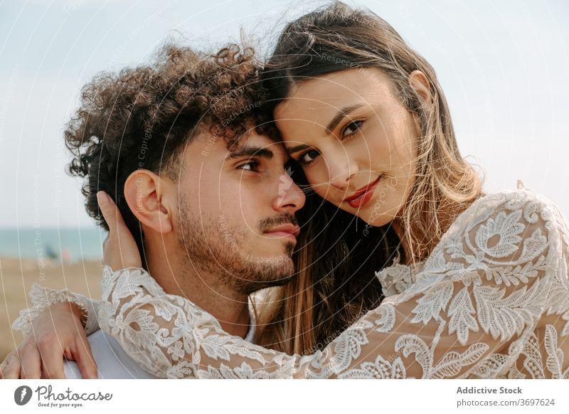 Glückliches frisch verheiratetes Paar umarmt am Strand romantisch Jungvermählter kuscheln sanft genießen Zusammensein Partnerschaft Liebe Umarmen Heirat Angebot