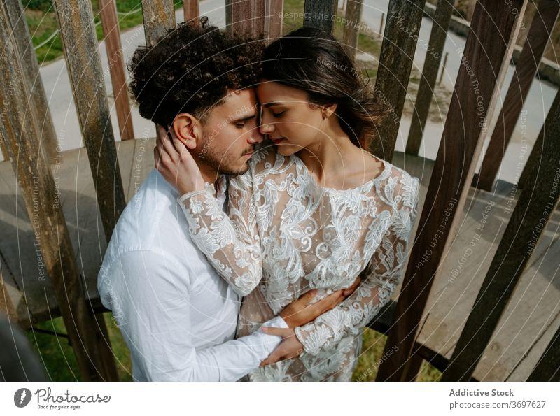 Loving junges Paar in Hochzeit Outfits umarmt auf Brücke romantisch Jungvermählter Umarmen kuscheln sanft Zusammensein Partnerschaft Liebe Angebot Heirat