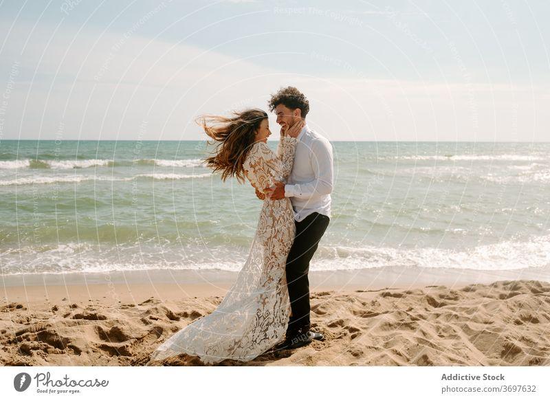 Glückliches frisch verheiratetes Paar steht gegen wogende Meer Jungvermählter Strand romantisch heiter Zusammensein Umarmen Partnerschaft MEER Liebe Natur Sand