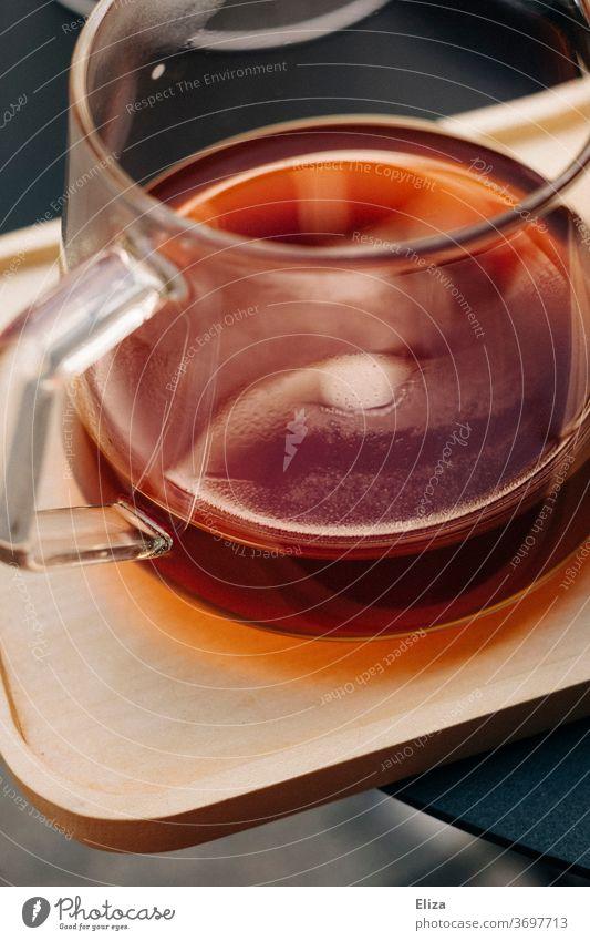 Eine Glaskanne mit frisch gebrühtem Kaffee auf einem Holztablett Kaffeekanne Filterkaffee Koffein aromatisch Tee Teekanne warm heiß Morgen Frühstück Getränk
