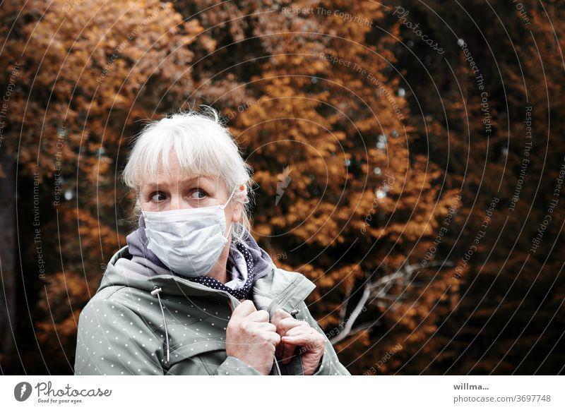 Angst vor Ansteckung Frau Mundschutz Ansteckungsgefahr Corona Herbst ängstlich besorgt fragend vorsichtig Seniorin Infektionsgefahr Prävention Ansteckend