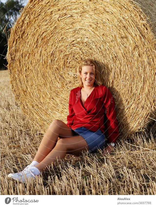 Portrait einer jungen Frau an einem Strohballen im Abendlicht junge Frau blond Lächeln rot Schmuck schön langhaarig Landschaft Wolken Himmel gebräunt