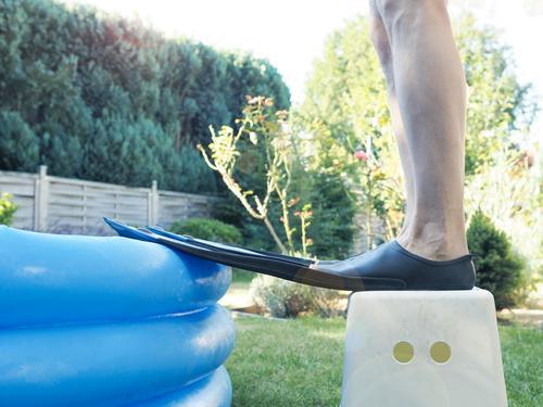 Mann mit Schwimmflossen steht vor einem kleinen aufblasbaren Becken. Sportler Training sportlich professionell passen aqua Fitness Athlet Badebekleidung
