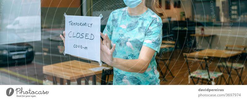 Frau platziert Coronavirus-Verschlusszeichen Platzierung Aushang Abschluss covid-19 Kaffeehaus Operationsmaske Klebeplakat Quarantäne Transparente Netz Kopfball