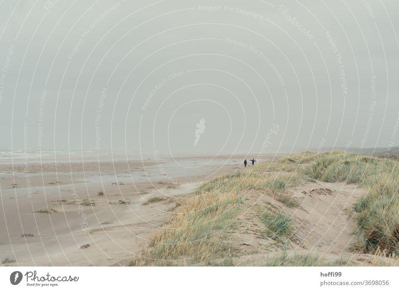 Strandspaziergang - wenig los bei Nieselregen Mensch Wattenmeer Nordsee nass Regen Wetter friedlich Einsamkeit Meer Küste Sand Wasser 2 Menschen Insel Ferne