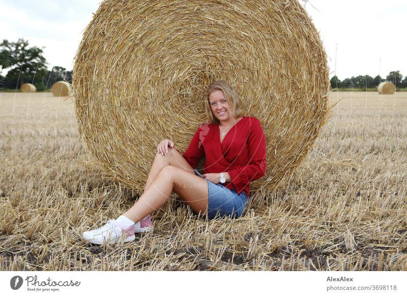 Junge Frau sitzt an einen Strohballen gelehnt auf dem Feld und lächelt Beine Freizeit Spaß Freude Jeans Ganzkörper Zentralperspektive Blick in die Kamera