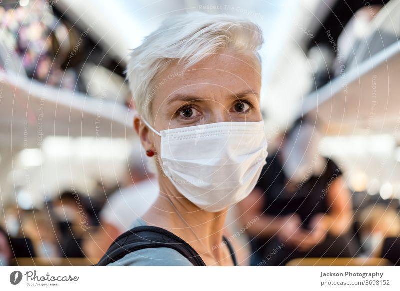Im Flugzeug stehende Frau mit Gesichtsmaske Mundschutz reisen Reisender Gang Innenbereich Lifestyle post-covid-19 Corona-Virus sicher neue Normale Ausbruch