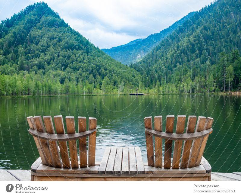 Zwei leere Holzliegenstühle am Strand, schöne Landschaft mit Bergsee, Urlaub in den Bergen, luxuriöses Sommerferienkonzept. See Natur Windstille reisen Himmel