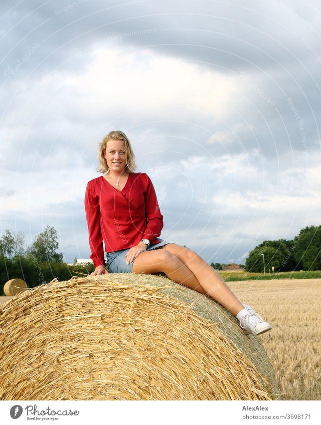Junge Frau sitzt auf einem Strohballen auf dem Feld und lächelt Beine Freizeit Spaß Freude Jeans Ganzkörper Zentralperspektive Blick in die Kamera